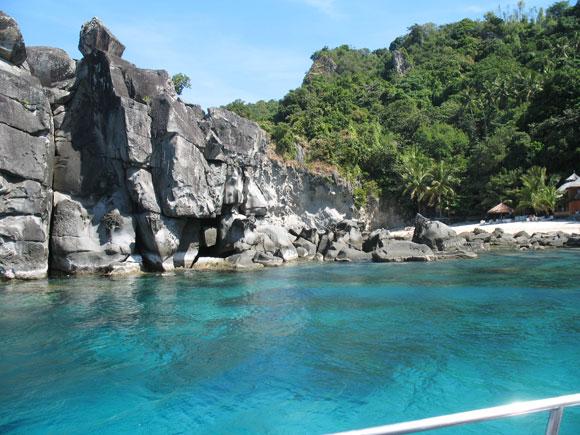 Apo Island beim Anlanden - türkisblaues klares Wasser, Felsen und Palmen.
